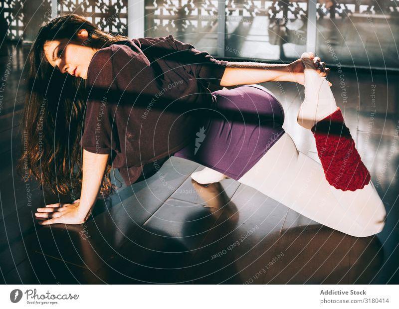 Ballerina-Tänzerin beim Aufwärmen des flexiblen Körpers im sonnigen Studio. Frau strecken üben Sport Balletttänzer Pose Aktion Dehnung Beautyfotografie