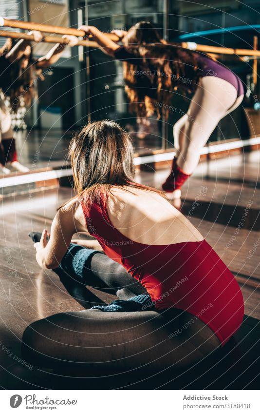 Junge Tänzerinnen und Tänzer trainieren gemeinsam im Studio beim Aufwärmen und Beugen im Sonnenlicht. Frau Balletttänzer Fitness üben Flexibilität Dehnung