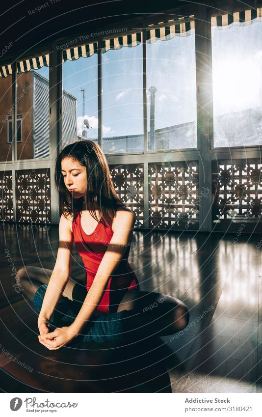 Zufriedene Frau, die ihren Körper im Studio beugt. Tänzer Studioaufnahme Dehnübung Dehnung sitzen Erholung beweglich sportlich Konzentration üben Innenaufnahme