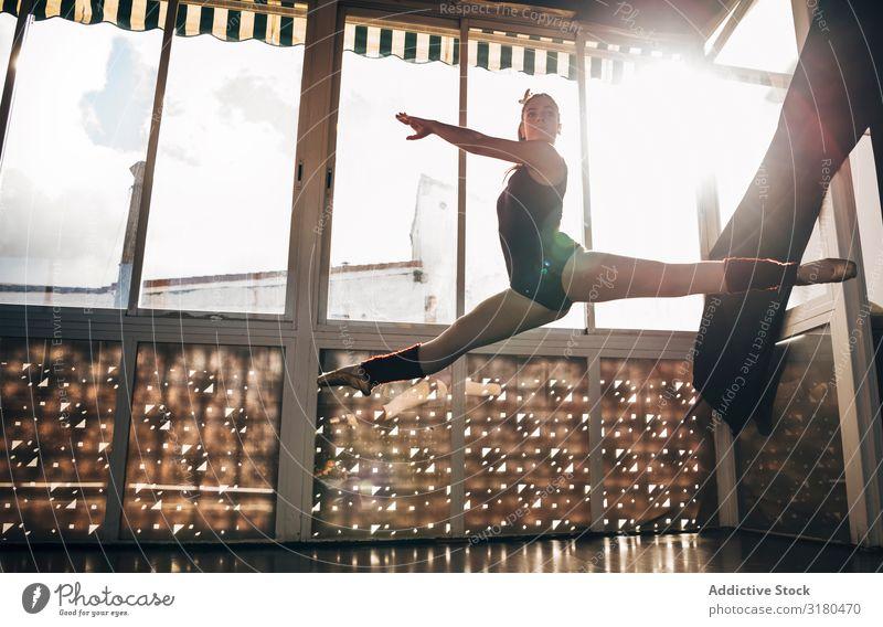 Junge schlanke Ballerina, die in Studiobeugebeinen über Grund springt. Frau springen Spagat Balletttänzer Pose Bewegung Akrobatik Turnen Tänzer Tanzen