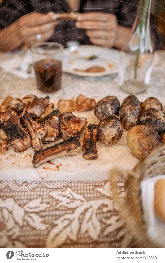 nicht erkennbare Personen, die Rippchen und Kartoffeln vom Grill essen. Abendessen Würstchen grillen Koch Gesundheit Außenaufnahme Mensch Hand Mittagessen