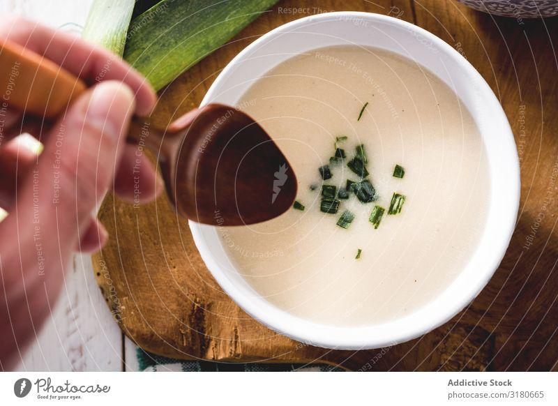 Gerte Hand mit Löffel und leckerer Vichyssoise Suppe auf Holztisch mit Lauch Vorspeise Schalen & Schüsseln Creme cremig Diät Lebensmittel Franzosen frisch