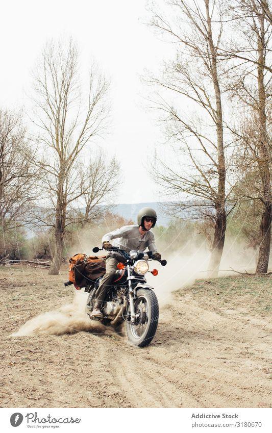 Mann fährt Motorrad auf staubiger Straße Ausritt Natur Ferien & Urlaub & Reisen Baum laublos Staub Landschaft Ausflug Verkehr Fahrzeug Laufwerk Freiheit