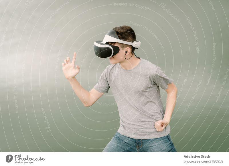 Junge Teenager mit Virtual-Reality-Brille im Freien virtuell Realität Brillenträger VR Jugendliche Natur Headset Technik & Technologie Spielen Zukunft 3d