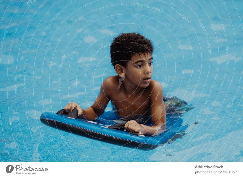 Schwarzer Junge schwimmt im Pool Schwimmbad Schwimmsport Wegsehen schwarz Sommer Glück Freude Wasser Ferien & Urlaub & Reisen Kind Afroamerikaner urwüchsig