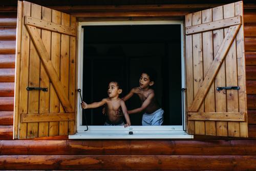 Schwarze Jungs schauen aus dem Fenster. Haus Holz offen Freude Zusammensein Afroamerikaner Kind