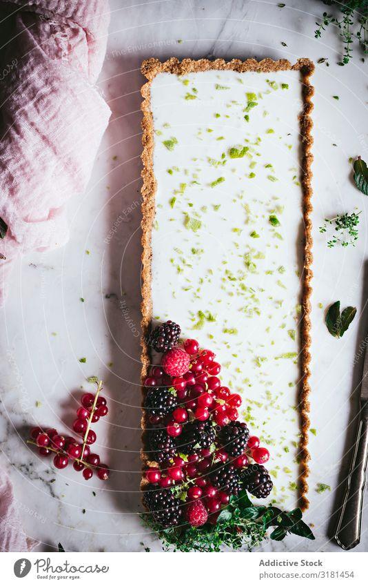 Limettenkuchen mit Beeren dekorierend Kuchen Dessert Lebensmittel süß geschmackvoll gebastelt lecker Tischplatte Himbeeren Stil kulinarisch Stillleben