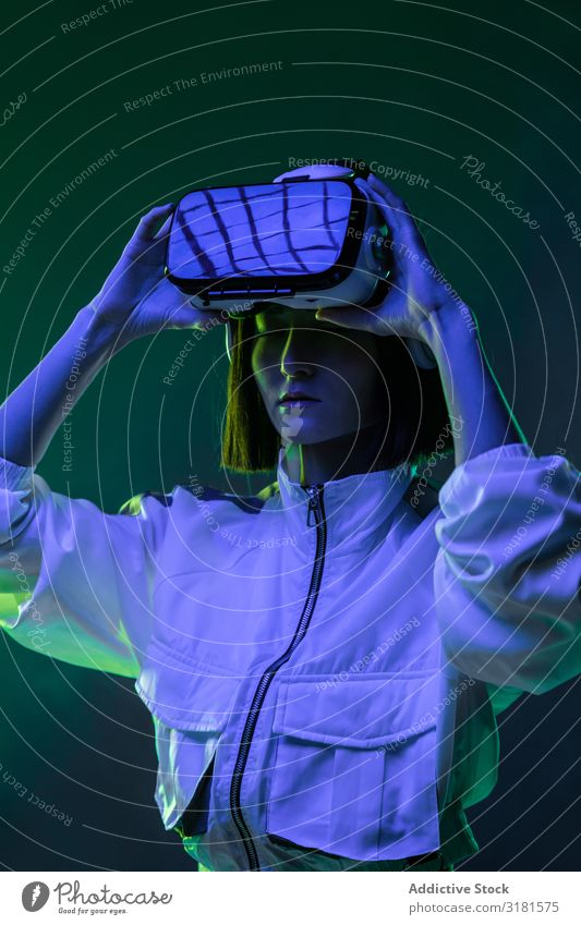 Frau im VR-Headset virtuell Realität Technik & Technologie neonfarbig Licht berühren Gerät digital Innovation Jugendliche Mensch Brillenträger asiatisch modern