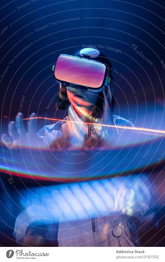 Frau berührt Luft in VR-Brillen asiatisch Headset Virtuelle Realität Technik & Technologie neonfarbig Licht berühren Gerät digital Innovation Brillenträger