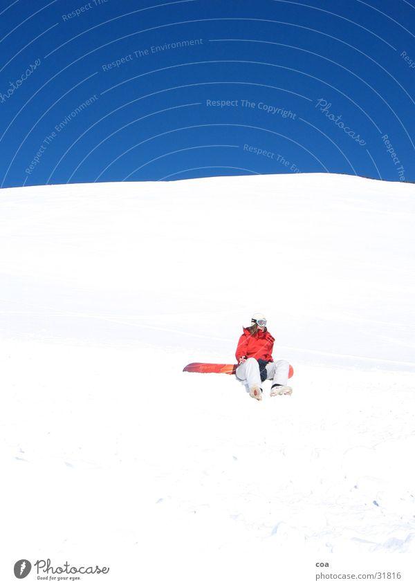Pause Himmel blau weiß rot ruhig Winter Schnee Sport sitzen einzeln Schönes Wetter Wolkenloser Himmel Snowboard hocken grell