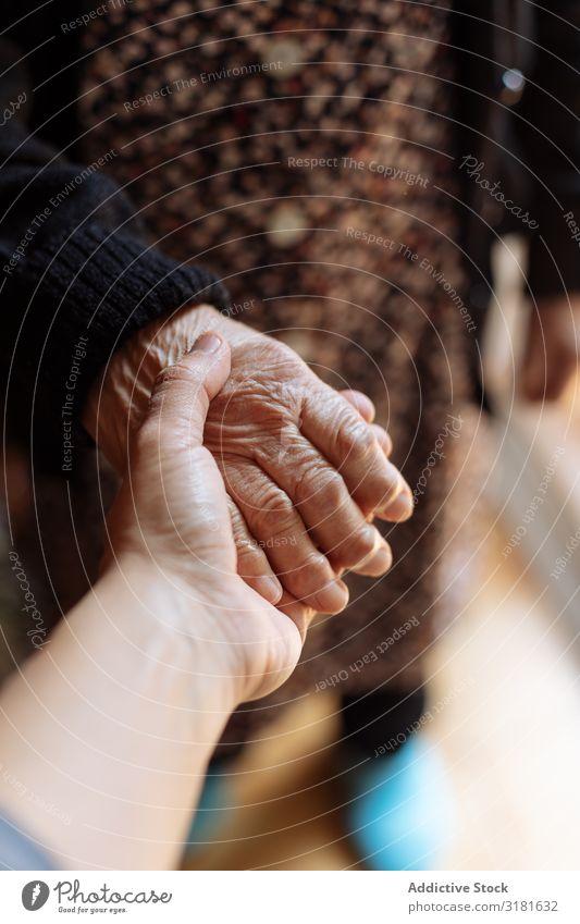 Mann hält die Hand einer älteren Frau. alt Halt Senior Jugendliche Enkel Großmutter abstützen Fürsorge Arzt Liebe Patient Hilfsbereitschaft Mensch Entwurf Hilfe