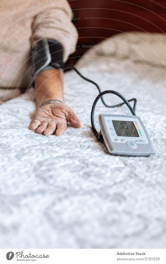 Älterer Mann überprüft seinen arteriellen Druck mit der Maschine. Werkzeug Blutdruck alt messen Krankheit Gesundheit Medikament Prüfung & Examen Erwachsene