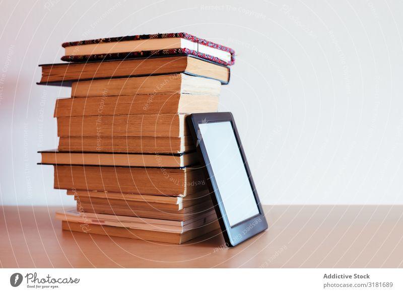 Vintage-Bücher neben einem E-Book modern alt altehrwürdig Technik & Technologie Postkarte neu Text digital Internet Bildung Wolken Schule Buchseite Anzeige