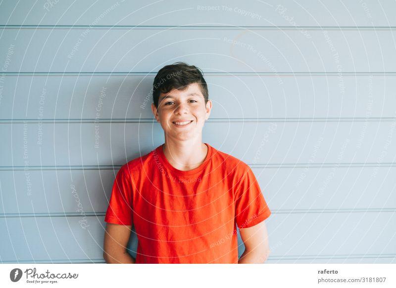 Fröhlicher männlicher Teenager, der sich an die Wand lehnt, während er die Kamera ansieht. Lifestyle Freude Glück Gesicht Fotokamera Mensch maskulin Junge Mann