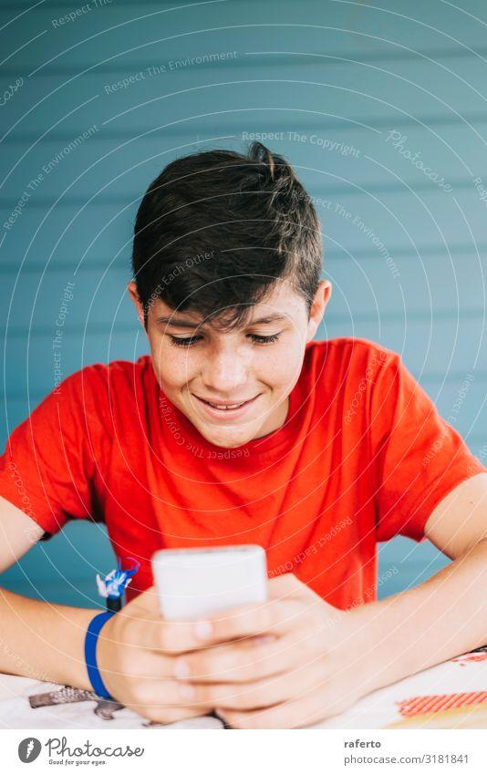 Junge im roten T-Shirt, der im Freien sitzt und telefoniert. Lifestyle Glück Freizeit & Hobby Telefon Handy PDA Technik & Technologie Mensch maskulin Mann