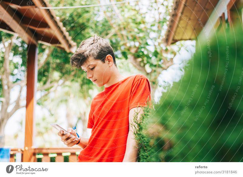 Profil eines glücklichen männlichen Teenagers, der auf einem Smartphone schreibt. Glück Telefon Handy PDA Mensch maskulin Junge Mann Erwachsene Jugendliche 1