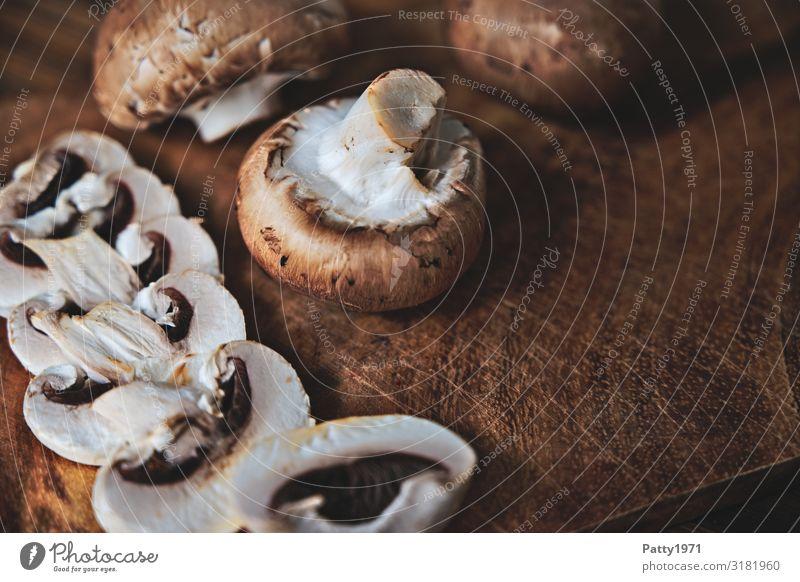 Champignons auf einem Holztisch Lebensmittel Pilz Ernährung Bioprodukte Vegetarische Ernährung Schneidebrett frisch lecker braun weiß genießen Foodfotografie