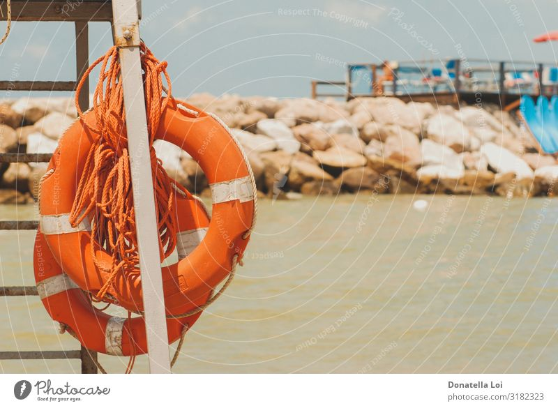Zwei orangefarbene Rettungsringe am Strand sparen Ferien & Urlaub & Reisen Tourismus Ausflug Sommer Meer Wärme Stein Sand maritim Schutz Sicherheit Überleben