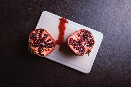 Granatapfel Gesunde Ernährung Gesundheit Lebensmittel Essen Frucht frisch genießen Bioprodukte wählen Vegetarische Ernährung Teilung Schneidebrett Hälfte