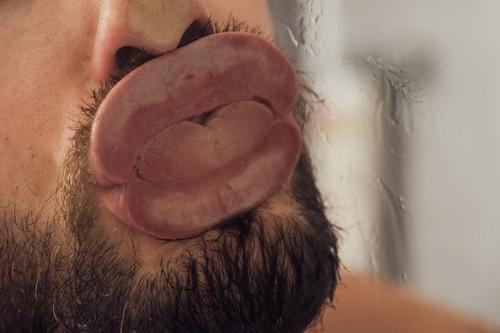 Ekliger Knutscher gegen eine Glasscheibe Zunge Mund Lippen Küssen schlecht Kuss knutschen Zungenkuss eklig bäh Belästigung Sexuelle Belästigung nass Dusche