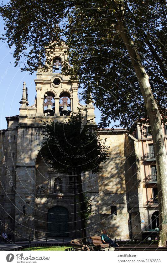 Ein Mann sitzt im Schatten auf einer Parkbank an einem Kirchplatz Kirche Bäume Platz Glockenturm Bilbao Sommer Sonne Bank Pause Erholung Außenaufnahme ruhig