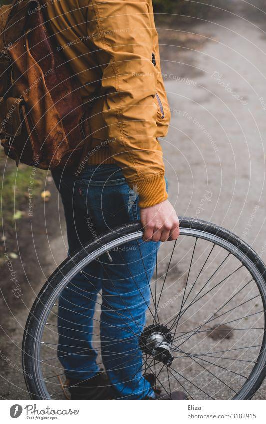 Ein Mann hält einen Fahrradreifen Mensch maskulin Junger Mann Jugendliche Erwachsene 1 18-30 Jahre Umweltschutz Rad Reifen Herbst Wege & Pfade Radrennen