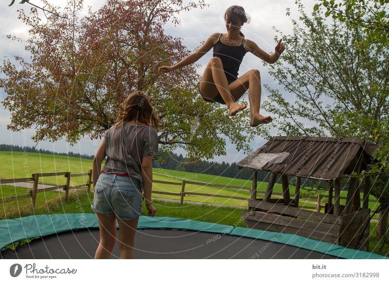 Zwei Mädchen hüpfen gemeinsam Trampolin, in der Natur. Eine fliegt hoch, die Schwester steht zum zuschauen, beobachten, lernen daneben. Sport Fitness Junge Frau