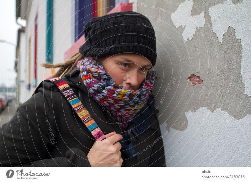 Vorderansicht einer jungen Frau mit Rastalocken, Mütze, buntem Schal und Tasche, welche in der Stadt, bei einem Ausflug müde, erschöpft, traurig an einer alten, grauen Hauswand mit buntem Fenster lehnt, um eine ruhige Pause zu machen.