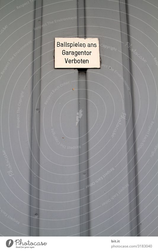 Text, Schriftzug, Hinweis, Warnung, Verbot: Ballspielen ans Garagentor verboten, steht auf einem weissen Schild, Tafel auf einem grauen Garagentor aus Blech, einer Garage in der Stadt, von einem bösen, unfreundlichen, kinderfeindlichen Nachbarn.