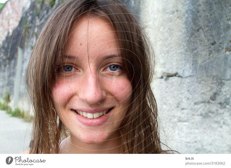 Hübsche brünette, langhaarige junge Frau, Teenager, Jugendliche lächelt natürlich in die Kamera,vor grauer Mauer im Urlaub. Fröhliches Mädchen mit blauen Augen, vor einem Felsen am Meer, in den Sommerferien am Strand, freut sich über Ferien und Sommerspaß.