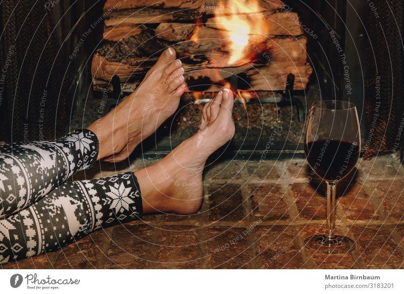 Frau ruht sich bei einem Glas Rotwein am Kamin aus. Alkohol Lifestyle Erholung Freizeit & Hobby Winter Haus Weihnachten & Advent Erwachsene Hand Wärme dunkel