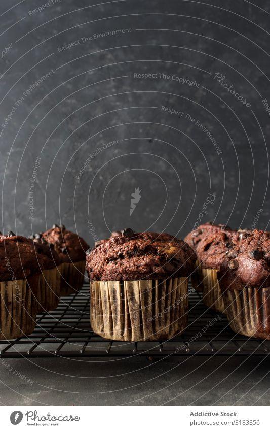 Schokobananen-Muffin auf Handtuch Banane Schokolade Wand grau Lebensmittel Cupcake Dessert frisch lecker geschmackvoll süß Kalorien Snack Backwaren Frühstück