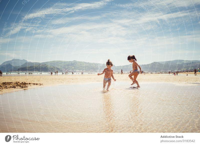 kleine Mädchen am Meer Strand Familie & Verwandtschaft Kind platschen Freude Sommer Glück Ferien & Urlaub & Reisen Wasser Mensch Lifestyle Spielen Natur Sonne