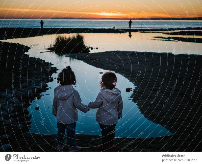 Rückansicht von kleinen Mädchen, die auf das Meer schauen. Kind Küste Fischer Silhouette Sonnenuntergang Ferien & Urlaub & Reisen Mensch niedlich Wasser