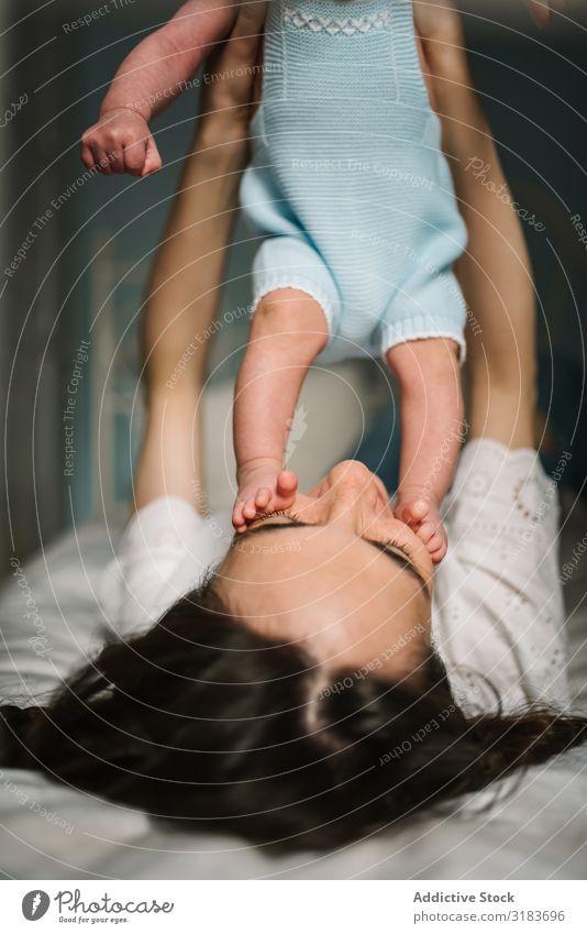 Mutter spielt mit dem Baby auf dem Bett. Fürsorge Angebot Familie & Verwandtschaft Liebe Frau Kind neugeboren harmonisch Idylle unschuldig ruhig Gelassenheit