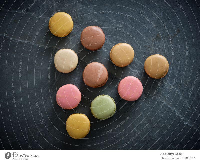 leuchtend frische, leckere Makronenkekse auf Graukarton Haufen Macaron mehrfarbig Biskuit Holzplatte geschmackvoll rosa Plätzchen hell Geschmack Zutaten Kulisse