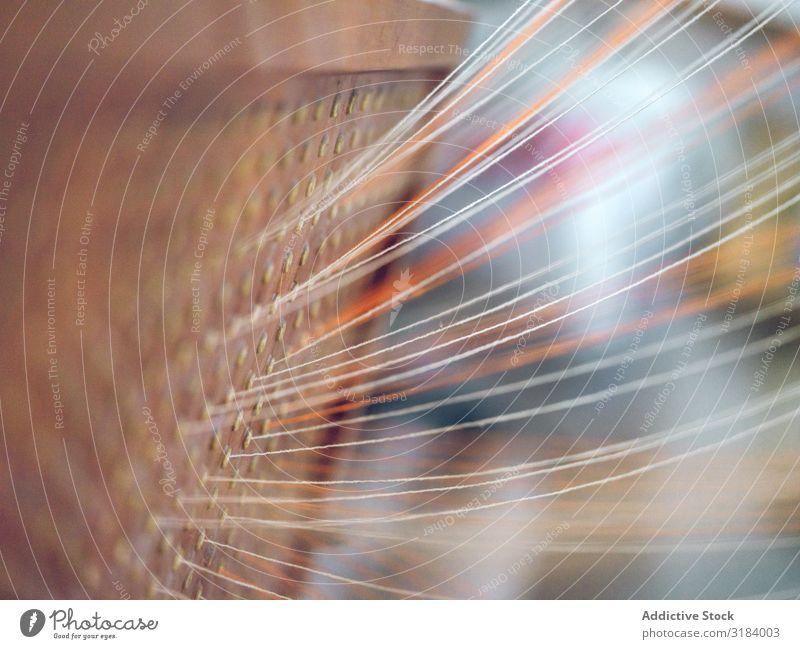 Weiße und orangefarbene Fäden auf dem Webstuhl Faser Industrie Baumwolle Textil Weberei Ballaststoff Stoff Fabrik Schnur Material Maschine Handwerk Tradition