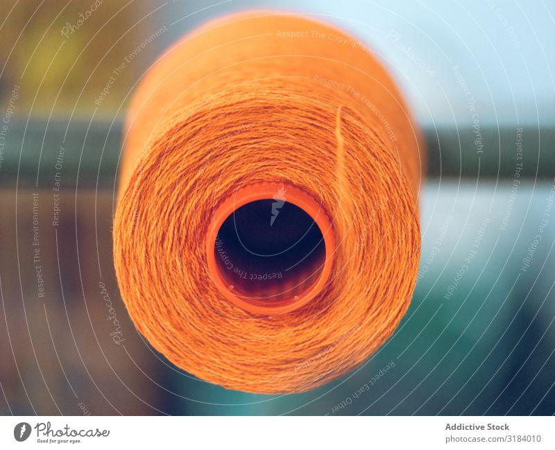 Garnrollen auf dem Webstuhl Faser Spulen Industrie Fabrik Ballaststoff Baumwolle Textil Stoff Maschine Produktion Schnur Handwerk Orange hell Farbe Material
