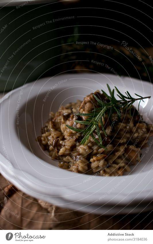 Rosmarin auf Risotto mit Kaninchen und Pilzen Reis Hase & Kaninchen Teller Tisch Küche rustikal Speise Abendessen Lebensmittel Fleisch Italienisch