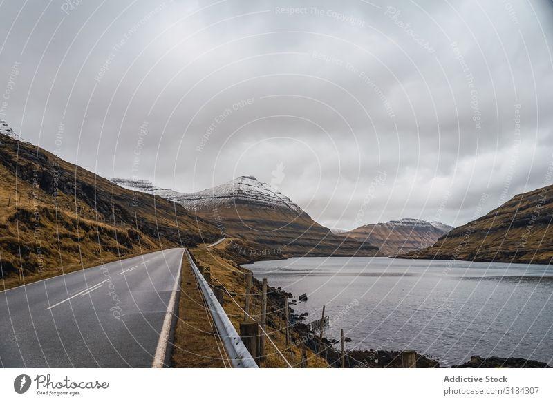 Wendelnde Straße auf hügeligem Gelände Hügel Landschaft geschlängelt Wolken Himmel Føroyar Ferien & Urlaub & Reisen Asphalt Wetter Natur ländlich Menschenleer