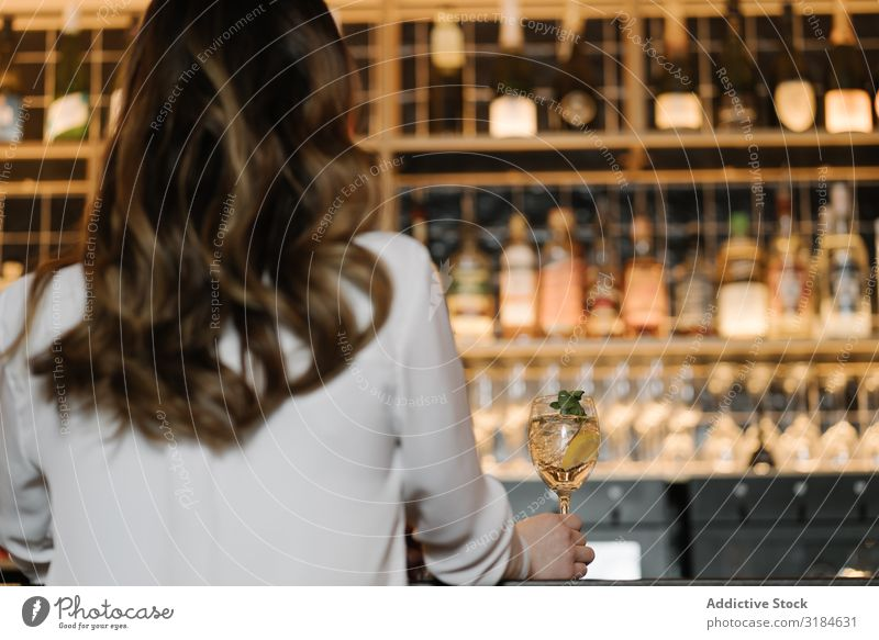 Rückansicht einer anonymen Frau, die einen Cocktail in der Bar hält. Restaurant gemütlich Party Alkohol Nacht Feste & Feiern Lifestyle Freizeit & Hobby ruhen