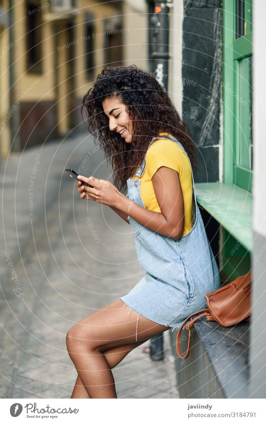 Junges arabisches Mädchen schaut draußen auf ihr Smartphone Lifestyle Stil Glück schön Haare & Frisuren Telefon PDA Technik & Technologie Mensch feminin