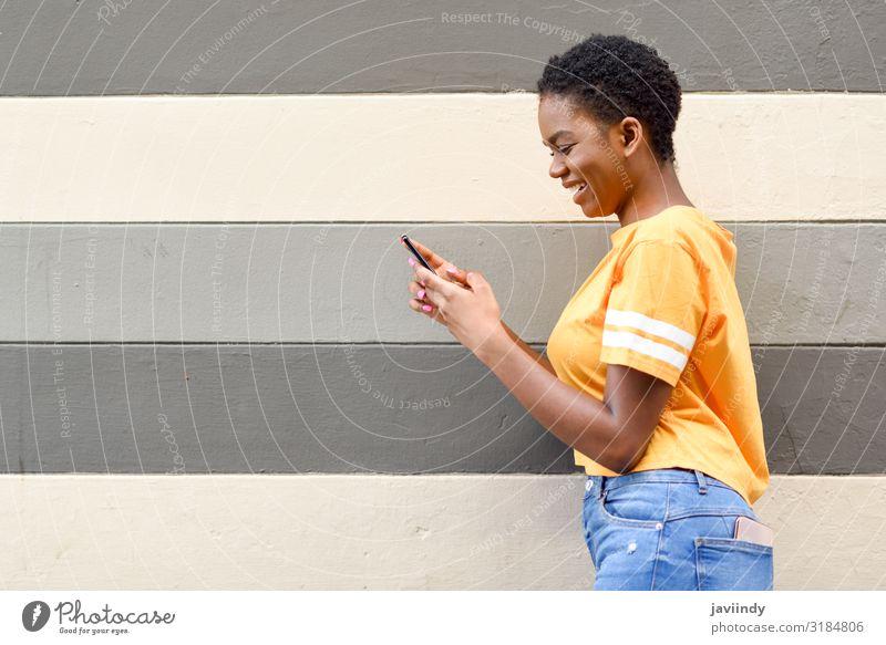 Junge schwarze Frau, die lachend ihr Smartphone im Freien benutzt. Lifestyle Stil Freude Glück Haare & Frisuren Telefon Funktelefon PDA Technik & Technologie