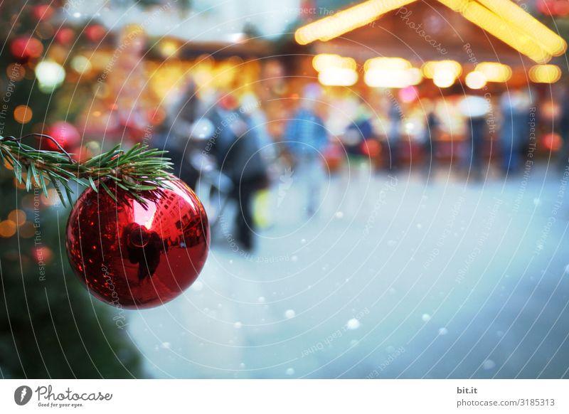 Unscharf l rote, glänzende Christbaumkugel, hängt an Tannenzweig in grün, auf beleuchteten Weihnachtsmarkt. Weihnachtsstimmung mit Christbaum auf Weihnachtsmarkt, beleuchtet mit viel Licht, in der Dämmerung. Abendstimmung auf Christkindlesmarkt mit Schmuck