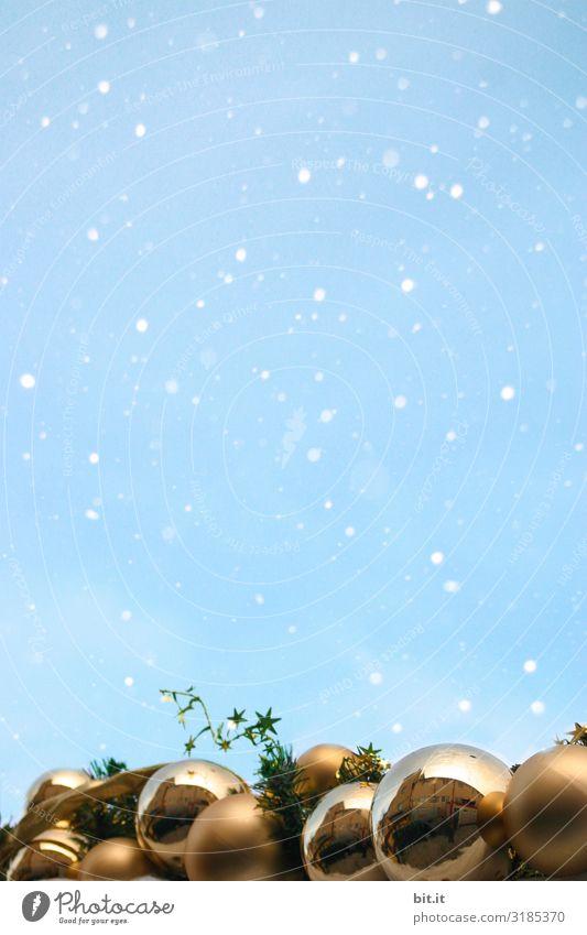 Glänzende, goldene Weihnachtskugeln im Schneefall vor blauem Himmel. Viele, funkelnde Christbaumkugeln im Schnee. Schneeflocken im Advent mit Weihnachtsdekoration, Verzierung unten. Kitschige Kugeln zur winterlichen, adventlichen, kalten Weihnachtszeit.