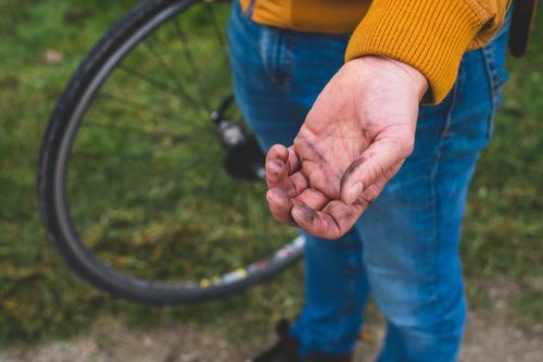 Dreckspatz Fahrradfahren dreckig Reparatur Fahrradreifen Hand Öl fahrradreparatur Mann Reifenpanne Farbfoto Außenaufnahme Tag Schwache Tiefenschärfe