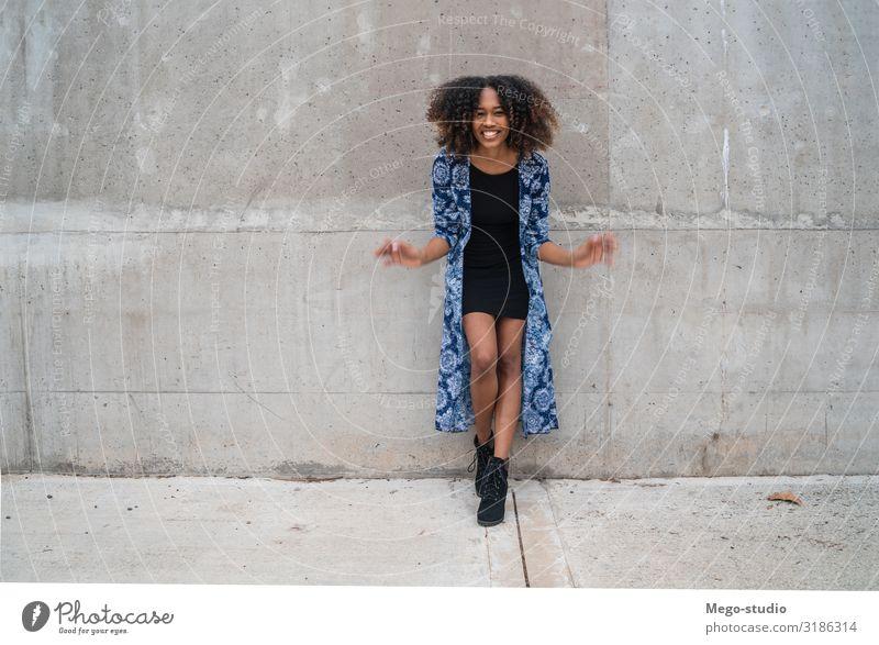 Afroamerikanische Frau gegen graue Wand. Stil Glück schön Gesicht Mensch Erwachsene Mode Bekleidung brünett Afro-Look Lächeln stehen Coolness Freundlichkeit