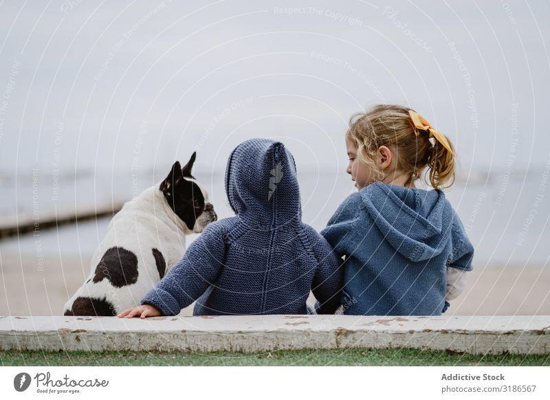 Kinder umarmender Hund am Strand Freundschaft Liebe Umarmen Haustier Meer sitzen gehorsam Baby französische Bulldogge lässig Lifestyle Freizeit & Hobby ruhen