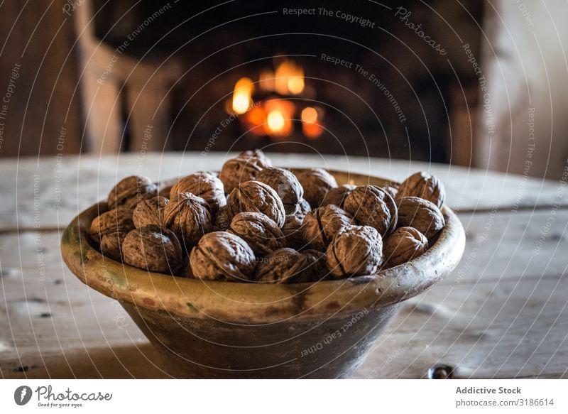 Schale mit Nüssen auf dem Tisch in einem alten Häuschen Haus Nuss Schalen & Schüsseln Feuerstelle bequem Küche Innenarchitektur Cottage Dorf Landschaft ländlich