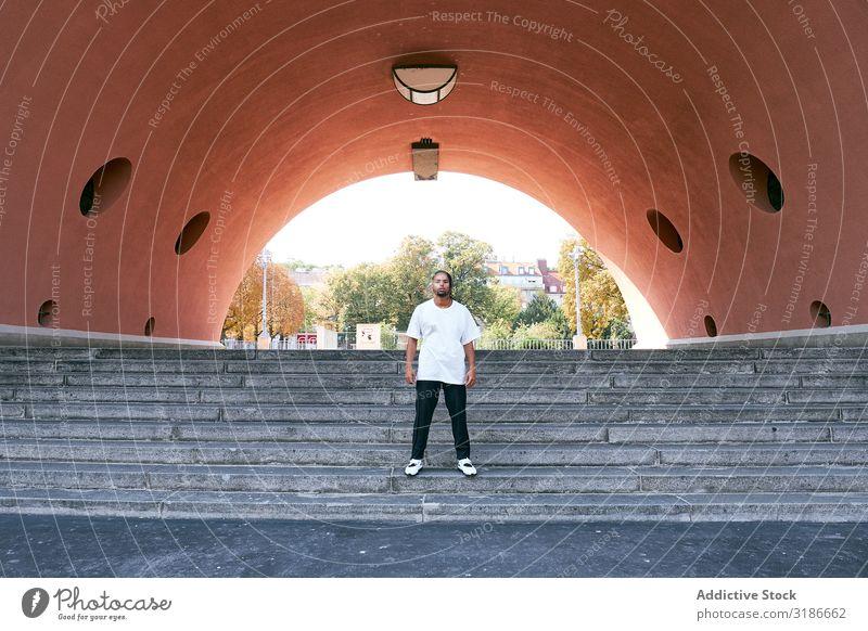 Trendy schwarzer Typ, der in der Nähe eines modernen Bogens posiert. Mann Straße Blick in die Kamera Afroamerikaner Mode modisch selbstbewußt Jugendliche Stil